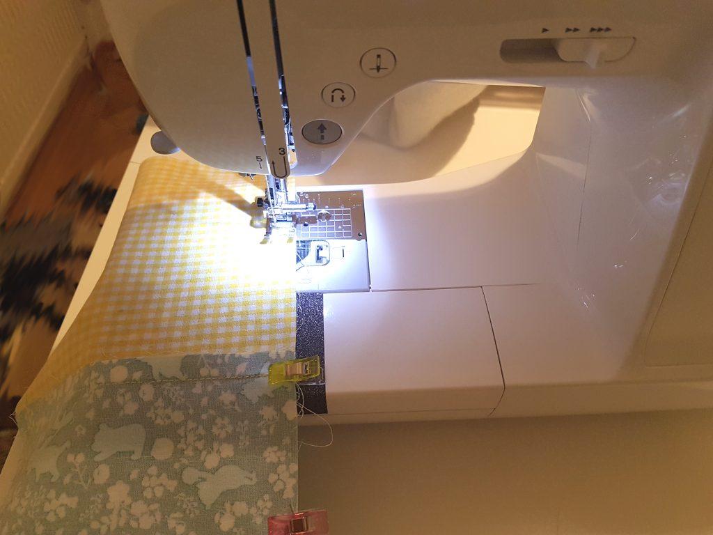 Quadrate für Patchworkdecke werden auf diesem Bild zusammengenäht