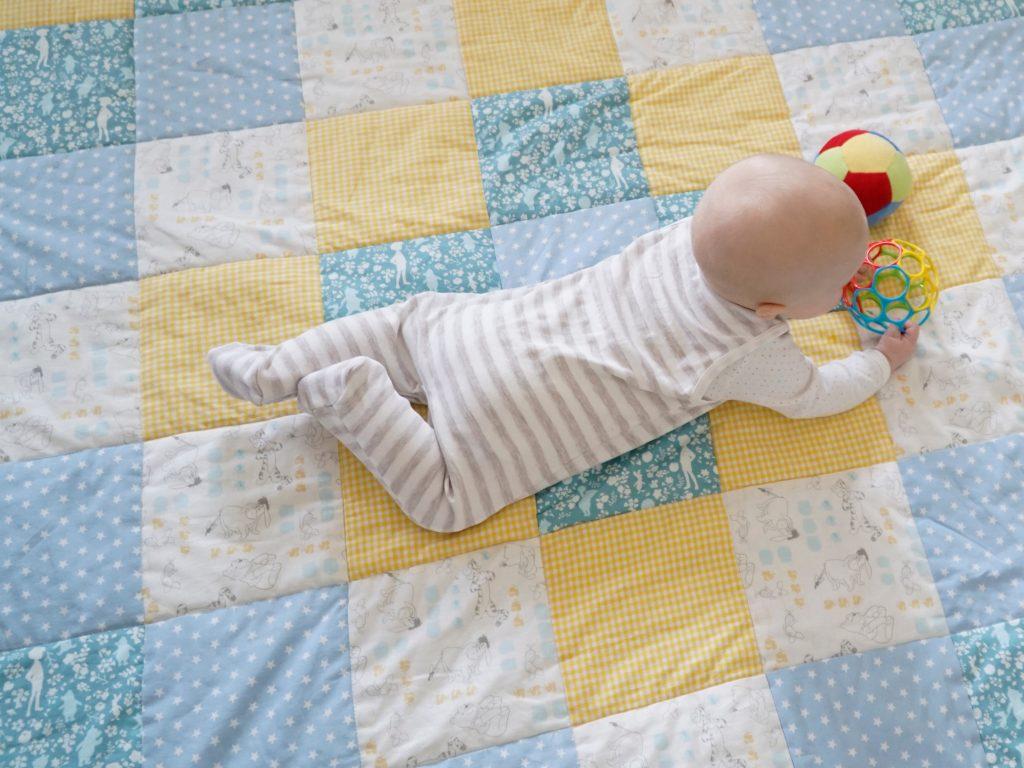 Baby auf der fertigen Patchworkdecke